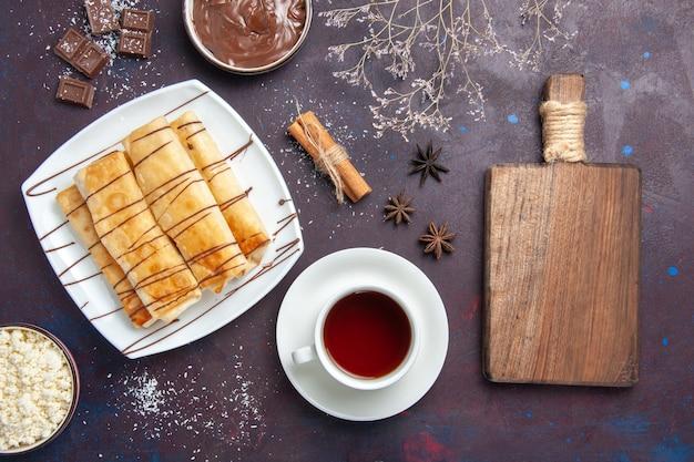 Vue de dessus de délicieuses pâtisseries sucrées avec du chocolat et une tasse de thé sur le sol noir