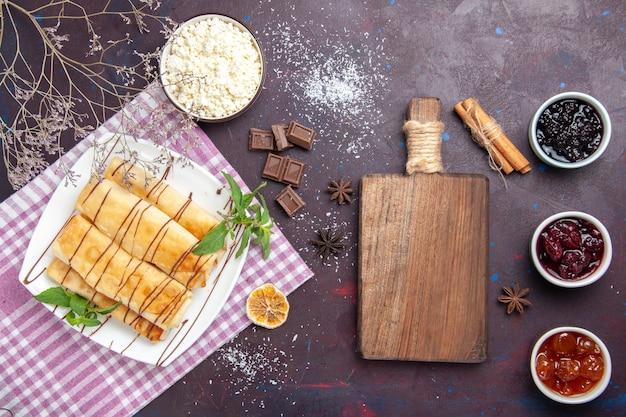 Vue de dessus délicieuses pâtisseries sucrées avec du fromage cottage et de la confiture sur fond sombre biscuit biscuit sucre gâteau sucré thé