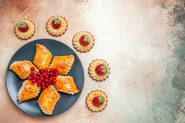 Vue de dessus de délicieuses pâtisseries sucrées fruits et biscuits sur une pâtisserie à tarte blanche sucrée
