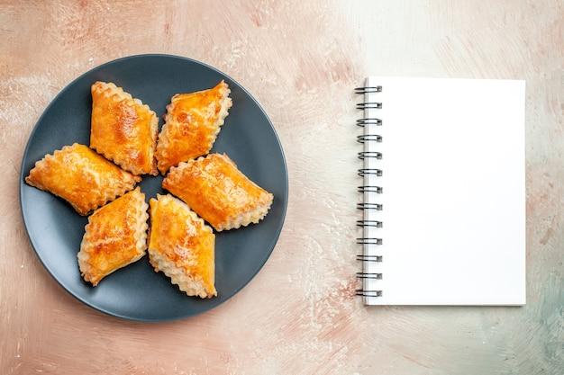 Vue de dessus de délicieuses pâtisseries sucrées à l'intérieur d'une assiette sur une tarte au gâteau sucré de pâtisserie au sol blanc