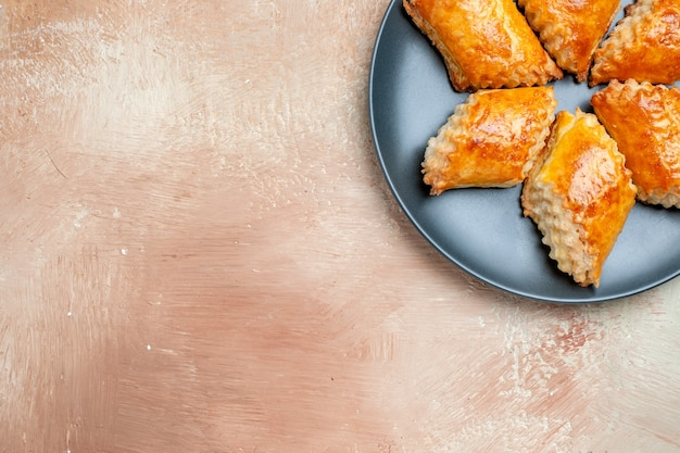 Vue de dessus de délicieuses pâtisseries sucrées à l'intérieur de la plaque sur une tarte sucrée de pâtisserie de gâteau de table blanc