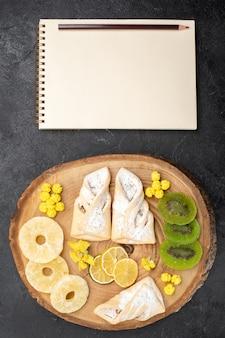 Vue de dessus de délicieuses pâtisseries avec des tranches de fruits secs sur un bureau gris