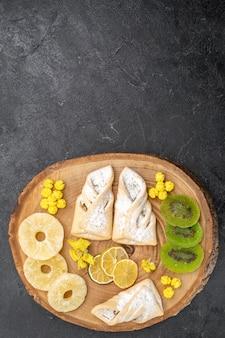 Vue de dessus de délicieuses pâtisseries avec des tranches de fruits secs sur l'espace gris