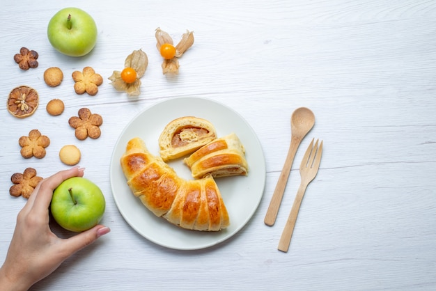 Vue de dessus de délicieuses pâtisseries en tranches à l'intérieur de la plaque avec remplissage avec pommes et biscuits sur un bureau blanc, biscuit pâtisserie biscuit sucre sucré