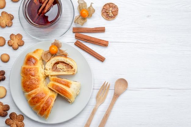 Vue de dessus de délicieuses pâtisseries en tranches à l'intérieur de la plaque avec remplissage avec thé cannelle et biscuits sur blanc, biscuit biscuit pâtisserie sucré