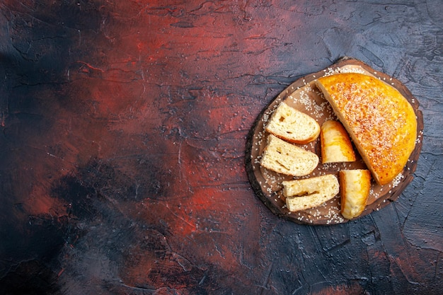 Vue de dessus de délicieuses pâtisseries en tranches sur la surface sombre