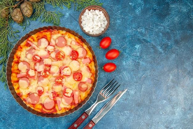 Vue de dessus de délicieuses pizzas au fromage avec des saucisses et des tomates sur fond bleu nourriture pâte gâteau couleur photo restauration rapide italien