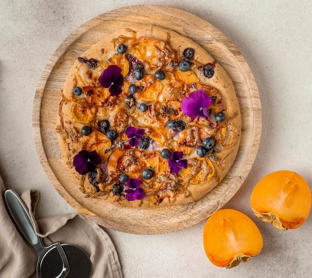 Vue de dessus de délicieuses pizzas cuites avec des kakis et des pétales de fleurs