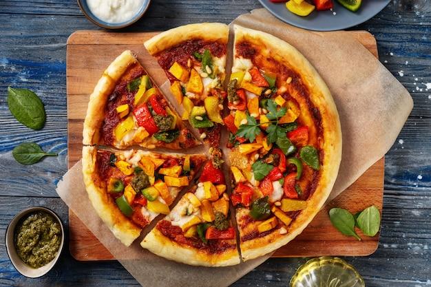 Vue de dessus de délicieuses pizzas végétaliennes coupées en morceaux