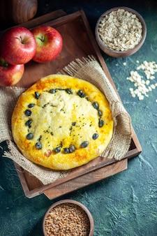 Vue de dessus de délicieuses pommes à pain sur planche de bois rectangle avoine et grains de blé dans des bols sur fond sombre