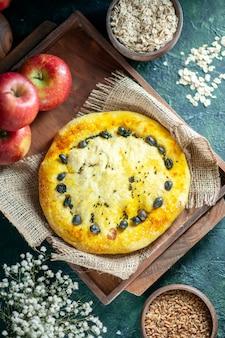 Vue de dessus de délicieuses pommes à pain sur planche de bois rectangle avoine et grains de blé dans des bols petites fleurs blanches sur table