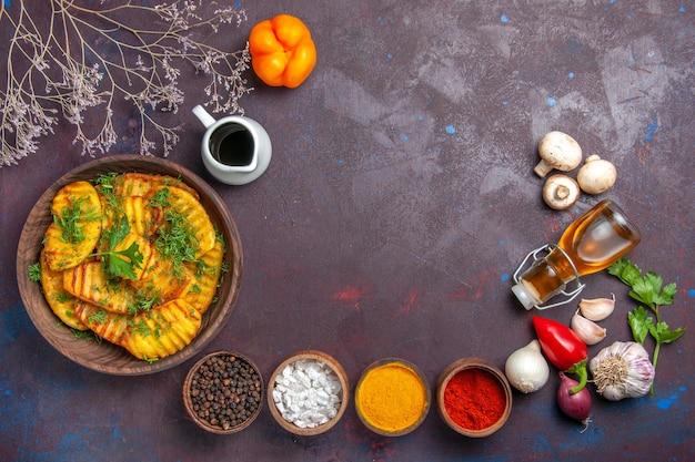 Vue de dessus de délicieuses pommes de terre cuites délicieux repas avec des légumes verts et des assaisonnements sur la surface sombre plat de pommes de terre plat de cuisson repas