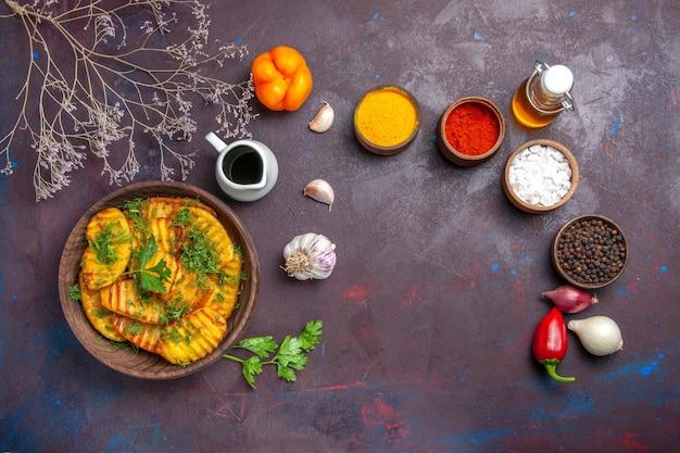 Vue de dessus de délicieuses pommes de terre cuites délicieux repas avec des légumes verts sur un bureau sombre