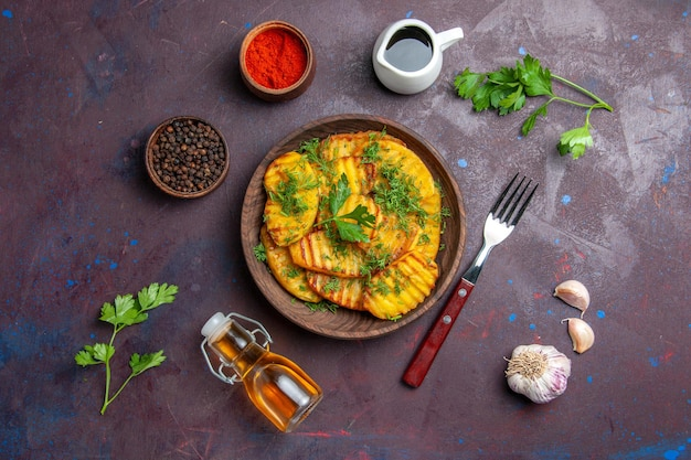 Vue de dessus de délicieuses pommes de terre cuites avec des légumes verts et des assaisonnements sur une surface sombre dîner de pommes de terre plat de repas cuisson cips