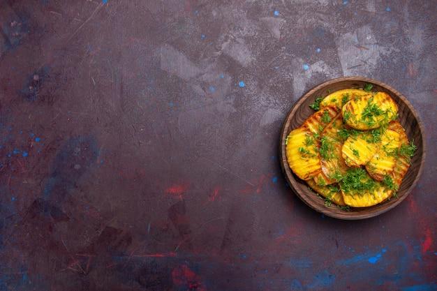 Vue de dessus de délicieuses pommes de terre cuites avec des légumes verts à l'intérieur de la plaque sur une surface sombre cuisson cips dîner nourriture pomme de terre