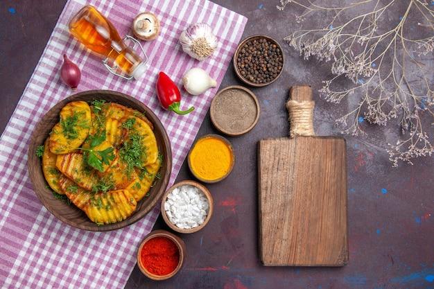 Vue de dessus de délicieuses pommes de terre cuites plat délicieux avec des légumes verts et des assaisonnements sur la surface sombre dîner de cuisson plat de pommes de terre