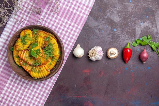 Vue de dessus de délicieuses pommes de terre cuites plat délicieux avec des légumes verts sur un bureau sombre plat de pommes de terre plat de cuisine repas