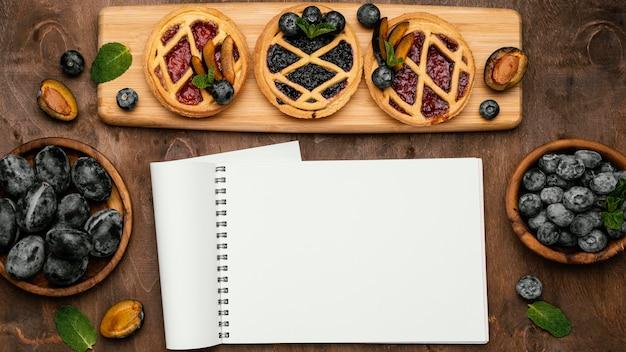 Vue de dessus de délicieuses tartes aux fruits avec prunes et cahier