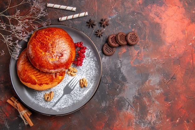 Vue de dessus de délicieuses tartes aux fruits rouges sur la tarte à la pâtisserie gâteau sucré table sombre