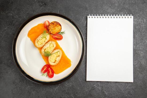Vue de dessus de délicieuses tartes aux pommes de terre avec de la citrouille à l'intérieur de la plaque sur une tranche de dîner de plat de couleur de cuisson au four de bureau gris