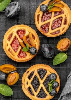Vue de dessus de délicieuses tartes aux prunes sur une grille de refroidissement