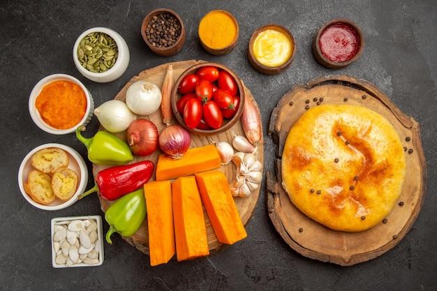 Vue de dessus de délicieuses tartes cuites au four avec des légumes sur une surface gris foncé