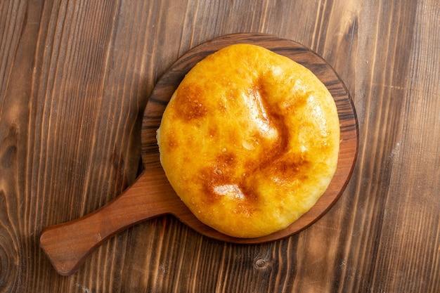 Vue de dessus de délicieuses tartes cuites au four avec de la purée de pommes de terre à l'intérieur sur le bureau en bois marron