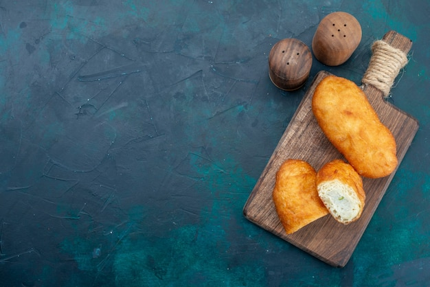 Vue de dessus de délicieuses tartes avec garniture de viande sur le bureau bleu foncé pâte à tarte pain bun cuire