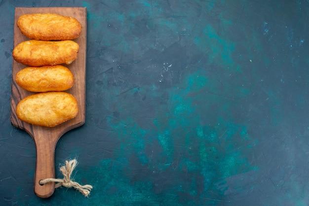 Vue de dessus de délicieuses tartes avec garniture de viande sur fond bleu foncé pâte à tarte pain pain alimentaire
