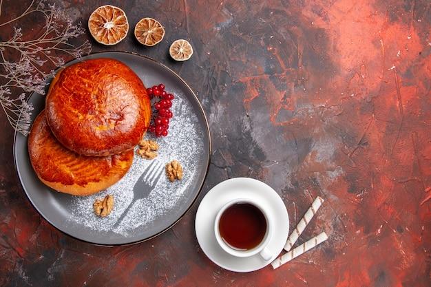Vue de dessus de délicieuses tartes avec une tasse de thé sur la table sombre pâtisserie gâteau tarte sucrée