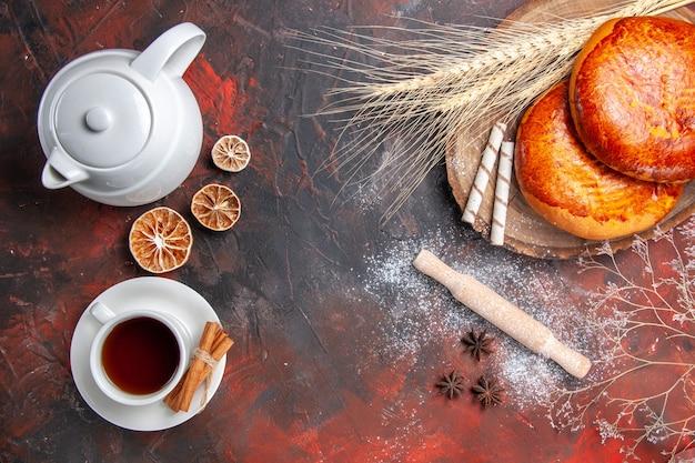 Vue de dessus de délicieuses tartes avec une tasse de thé sur une tarte sucrée de pâtisserie gâteau de table sombre