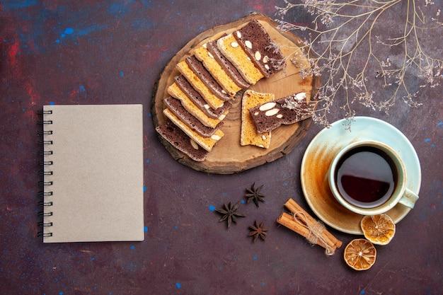 Vue de dessus de délicieuses tranches de gâteau aux noix et tasse de thé sur fond noir