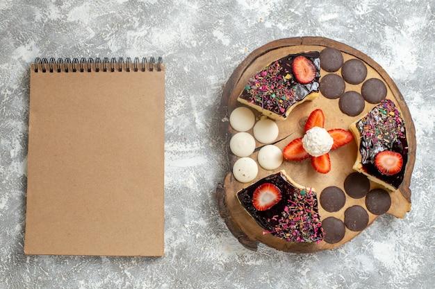 Vue de dessus de délicieuses tranches de gâteau avec des biscuits au chocolat sur une surface blanche