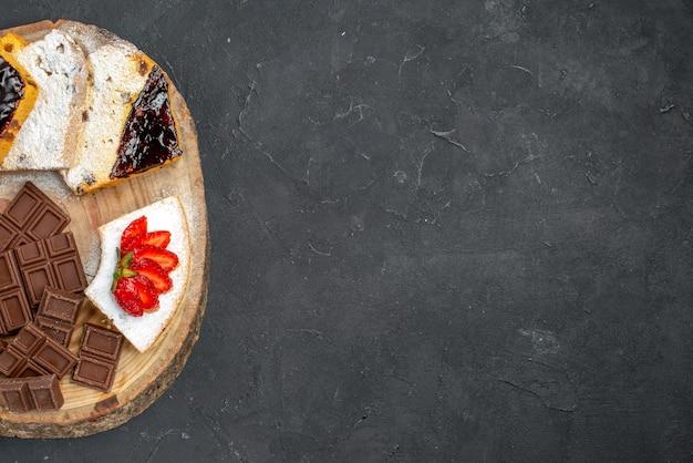 Vue de dessus de délicieuses tranches de gâteau avec des fraises et des barres de chocolat sur une surface sombre