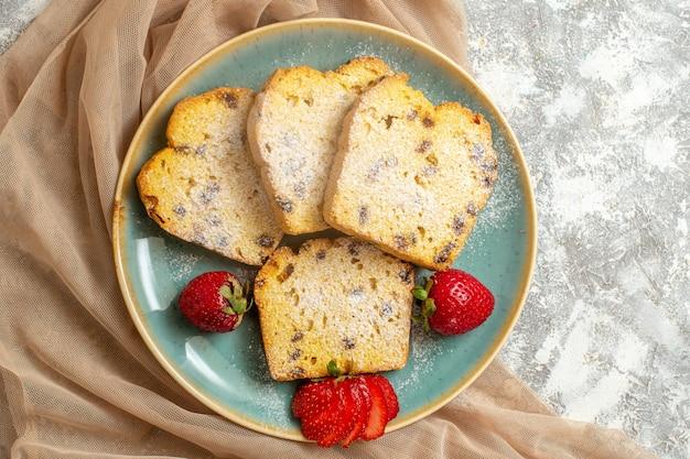 Vue de dessus de délicieuses tranches de gâteau avec des fraises fraîches à la lumière