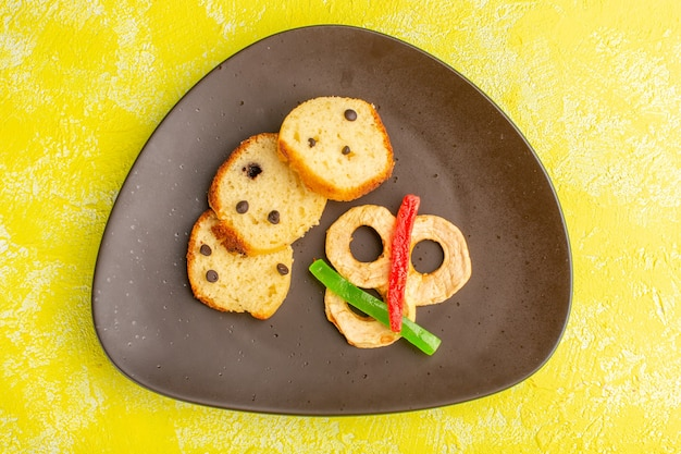 Vue de dessus de délicieuses tranches de gâteau à l'intérieur de la plaque brune avec de la marmelade sur la surface jaune
