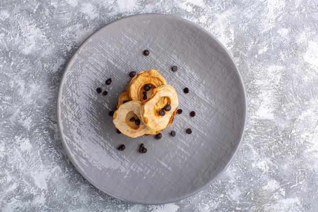 Vue de dessus de délicieuses tranches de gâteau à l'intérieur de la plaque avec des chips de chocolat sur une surface gris clair