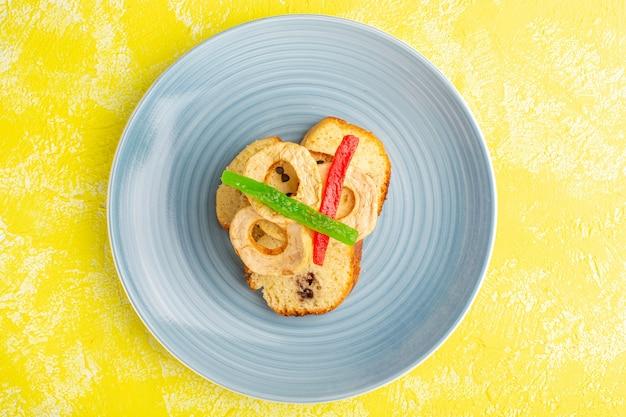 Vue de dessus de délicieuses tranches de gâteau à l'intérieur de la plaque avec de la marmelade sur une surface jaune