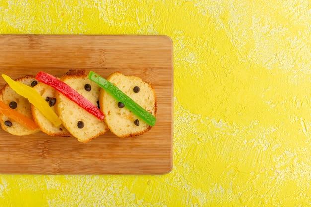 Vue de dessus de délicieuses tranches de gâteau avec de la marmelade sur une surface jaune