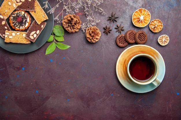 Vue de dessus de délicieuses tranches de gâteau avec une tasse de thé sur fond noir