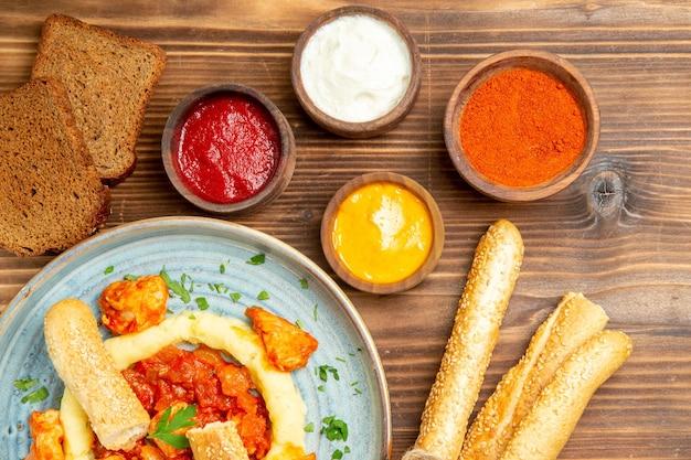 Vue de dessus de délicieuses tranches de poulet avec purée de pommes de terre et assaisonnements sur un bureau en bois repas de pommes de terre nourriture poivre épicé