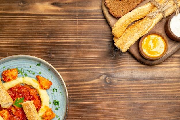 Vue de dessus de délicieuses tranches de poulet avec purée de pommes de terre et pain sur un bureau en bois repas de pommes de terre nourriture poivre épicé