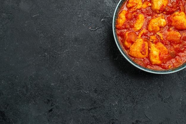 Vue de dessus de délicieuses tranches de poulet à la sauce tomate sur un plat de sauce au sol gris viande poulet tomate