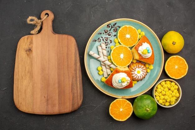 Vue de dessus de délicieuses tranches de tarte avec des biscuits à la pipe et des mandarines fraîches tranchées sur fond sombre tarte aux fruits tarte biscuit sucré