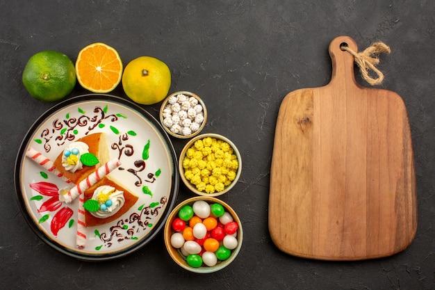 Vue de dessus de délicieuses tranches de tarte avec des bonbons et des mandarines fraîches sur le fond sombre gâteau aux fruits de tarte aux biscuits sucrés