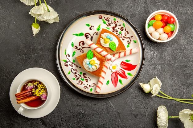 Vue de dessus de délicieuses tranches de tarte à l'intérieur de la plaque conçue avec une tasse de thé sur fond gris