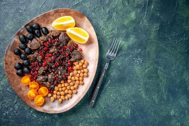 Vue de dessus de délicieuses tranches de viande frites avec des raisins de haricots et des tranches de citron à l'intérieur de la plaque