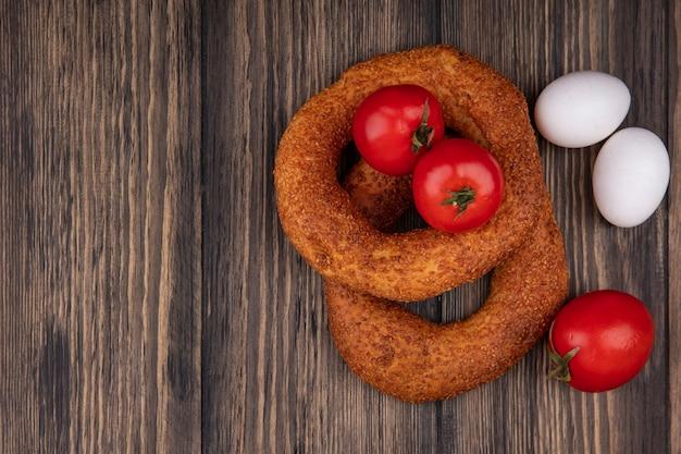 Vue de dessus de délicieux bagels au sésame turc avec des tomates et des œufs isolés sur un fond en bois avec espace copie