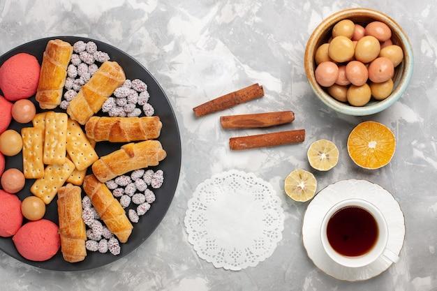 Vue de dessus de délicieux bagels avec des craquelins à la cannelle et des biscuits sur un biscuit de gâteau de bureau blanc léger