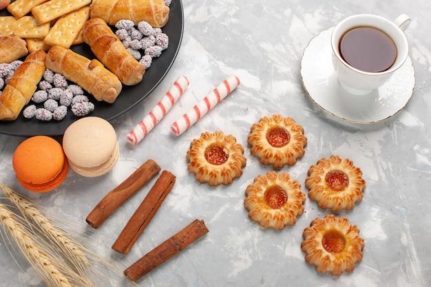 Vue de dessus de délicieux bagels avec des craquelins macarons et biscuits sur le gâteau de bureau blanc clair biscuit tarte au sucre sucré biscuit croustillant